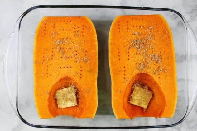 "The two butternut squash halves contain holes from a fork all over the flesh side. Both halves sit in a glass 9"" x 13"" pan, filled with a half inch of water. A pat of butter, some brown sugar, salt, and pepper sit in the hollowed out part of each butternut squash."