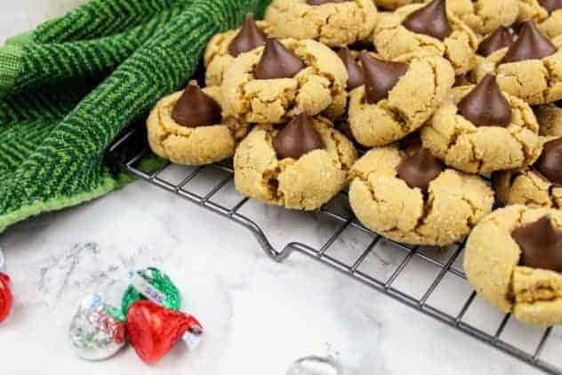 Healthier peanut butter blossoms sit on a wire cooling rack in the upper right corner. In the upper left corner, is a dark green kitchen towel. Scattered about in the foreground are red, green, and silver foil wrapped Hershey kisses. This is the horizontal image.