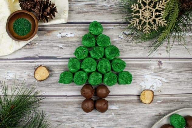 In the center are green and brown colored chocolate peanut butter balls arranged in the shape of a Christmas tree. Near the Christmas tree is an open peanut butter ball. Sprigs of fake evergreen trees sit in the lower left and the upper right. A gold snowflake also sits in the upper right. In the lower right are more peanut butter balls on a white plate. In the upper left is an ivory colored piece of cloth with gold glitter swirls, a cluster of pine cones, and a small dark brown wooden bowl of green sparkling sugar sprinkles. Everything sits on a wooden plank background. This is the horizontal image.