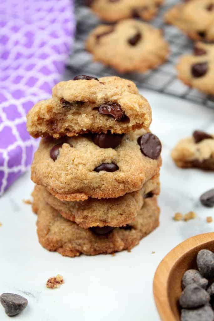 A stack of four dairy free chocolate chip cookies sits front and center. The top cookie is broken in half to show the texture of the interior. In the lower right is a small wooden bowl with chocolate chips. In the upper left is a light purple tea towel. In the upper right is a wire cookie rack with more dairy free chocolate chip cookies. Scattered about are crumbs and chocolate chips. Everything sits on a white marble background. This is the vertical photo.