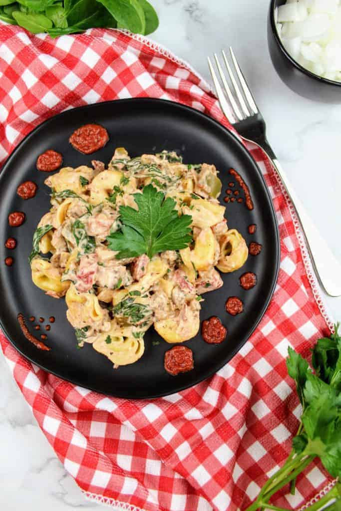 Creamy Tortellini with Sausage and Spinach sits on a black plate, garnished with a sprig of flat leaf parsley. Around the perimeter of the plate is an intricate design made with tomato sauce. On the right is a fork. In the upper left is a pile of spinach. In the upper right is a small black bowl of chopped onions. In the lower right is a bunch of flat leaf parsley. The plate sits on a white and red checkered tea towel. Everything sits on a white marble background.