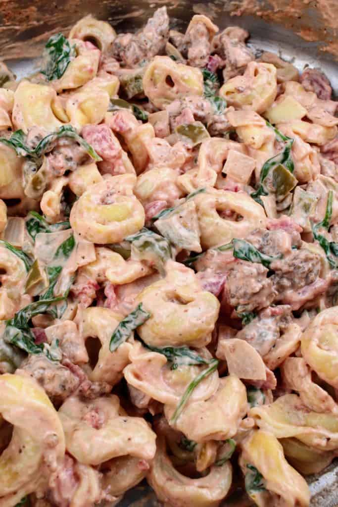 Addition of cooked tortellini to the mixture of spinach, browned sausage, diced tomatoes, cream cheese, Italian seasoning, bell pepper, onion, and garlic in a stainless steel pan.