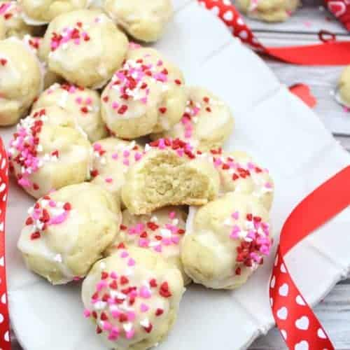 Gluten-free ricotta cookies sit on a scalloped cream colored serving tray. On top of the pile is half of a cookie to show the fluffy interior texture. A red ribbon with white hearts weaves throughout the photo. In the upper right is a Valentine's Day themed tea towel and two more gluten-free ricotta cookies. Scattered throughout the photo are red, white, and pink heart sprinkles and red heart confetti. Everything sits on a wood plank background. This is the horizontal photo.
