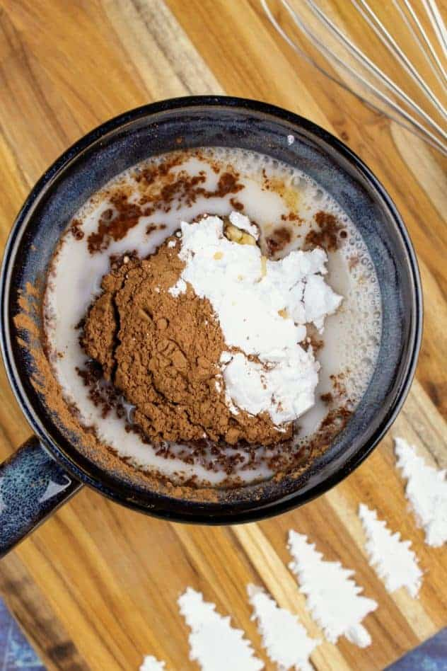 Addition of cocoa powder, confectioner's sugar, and vanilla extract to the mug filled with almond milk. The whisk sits in the upper right. At the bottom of the cutting board are pine trees made of confectioner's sugar. The cutting board sits on a navy blue background.