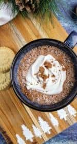In the center is a navy colored mug filled with vegan hot cocoa. It is topped with a swirl of coconut whipped cream and cocoa powder. Off to the left are two shortbread cookies and a white tea towel. At the top is a sprig of evergreen and pine cones. In the upper right is a small dark wooden bowl of marshmallows. Everything but the marshmallows sit on a wooden cutting board, the bottom of which has a line of evergreen trees made of confectioner's sugar. Everything sits on a navy blue background. This is the vertical image.