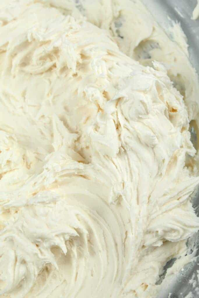 Vegan vanilla frosting sits in a large glass mixing bowl.