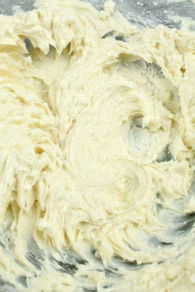 Vegan vanilla frosting after mixing in one cup of confectioner's sugar to the creamed mixture in a large glass bowl.