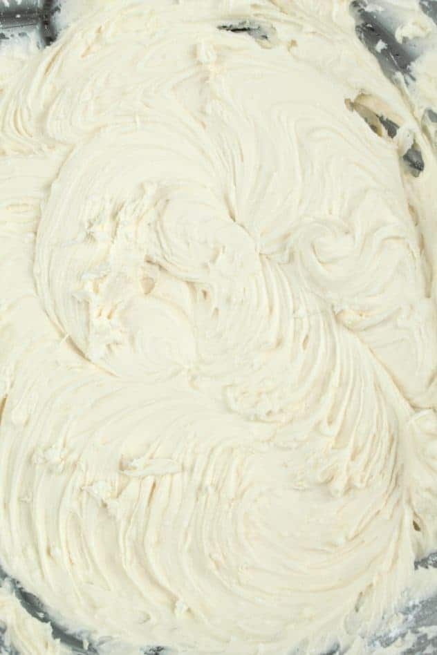 Vegan vanilla frosting after mixing in two cups of confectioner's sugar to the creamed mixture in a large glass bowl.