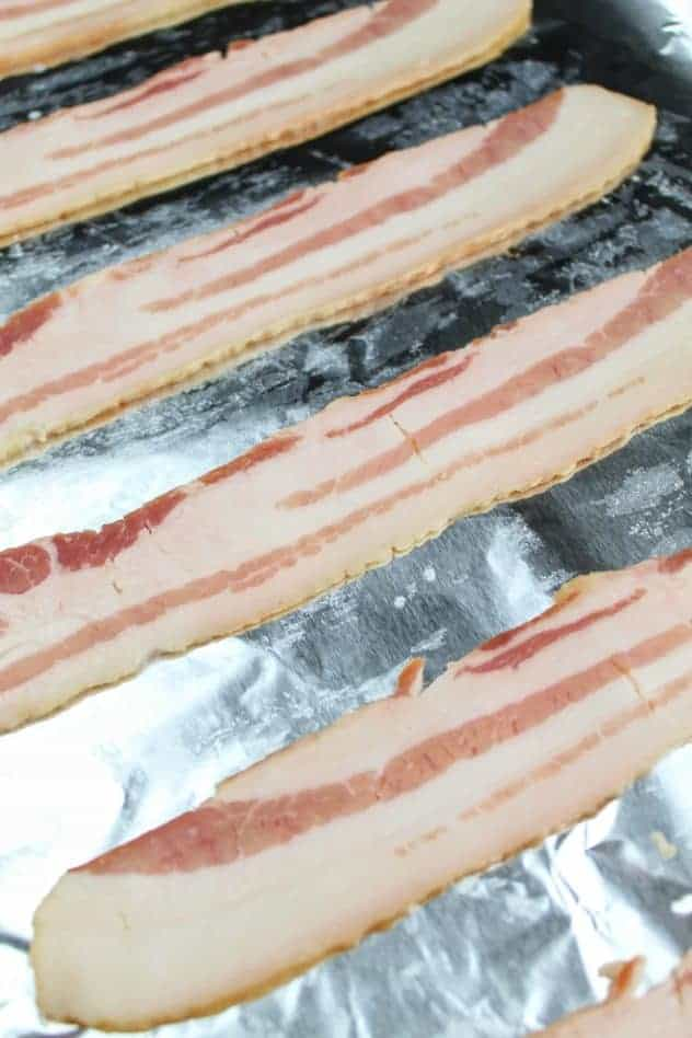 Raw applewood smoked bacon on an aluminum foil lined rimmed baking sheet.