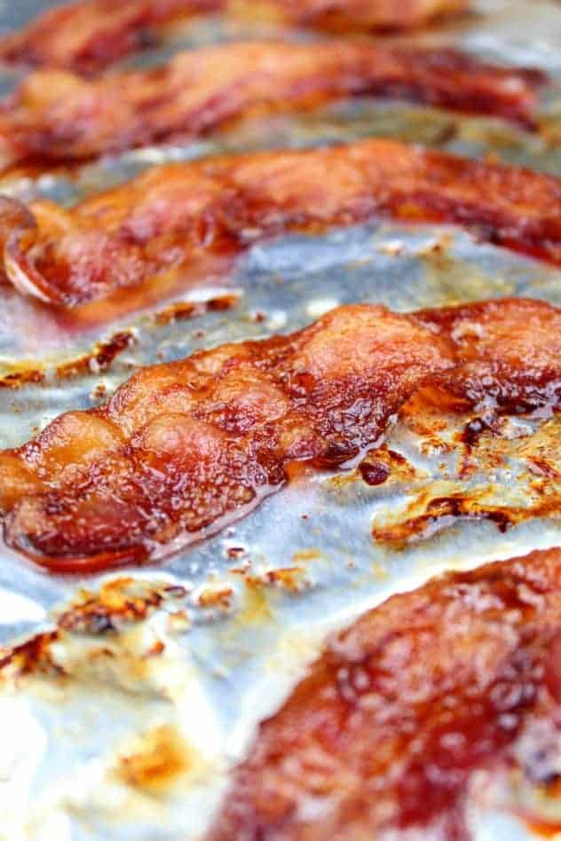 Oven baked bacon on an aluminum foil lined rimmed baking sheet. This is the vertical image.