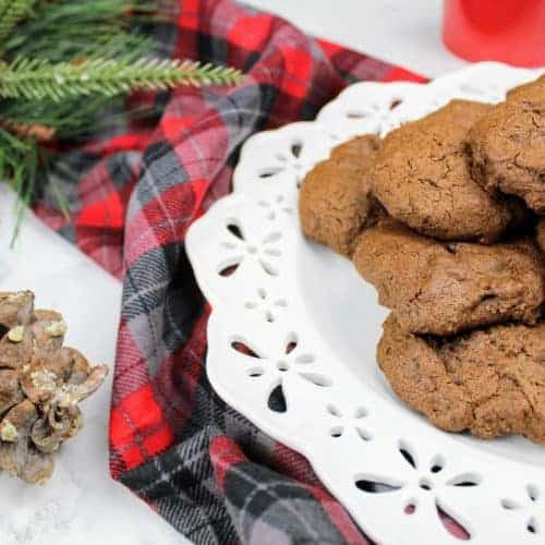 Chewy molasses cookies sit in a pile on a white plate. Off to the left is a pine cone and a sprig of evergreen. In the upper right is a red mug. Running through the picture is a gray, black, and red plaid pattern piece of fabric. Everything is on a white marble background. This is the horizontal image.