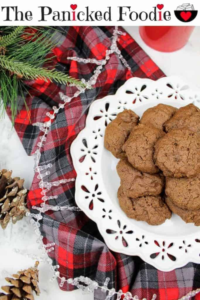 Chewy molasses cookies sit in a pile on a white plate. Off to the left are two pine cones, and a sprig of evergreen. In the upper right is a red mug. Running through the picture is a gray, black, and red plaid pattern piece of fabric. A strand of icicles weaves throughout the photo. Everything is on a white marble background. At the top of the image are the words 'The Panicked Foodie,' with the i's colored red and dotted with red hearts. At the end is a black mixing bowl with a red heart on it that contains three sugar cubes.