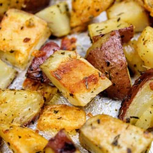Roasted herb red potatoes sitting on a textured aluminum baking sheet. The potatoes are golden brown and wrinkled from roasting in the oven. This is the horizontal image.