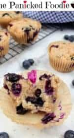 In the center of the picture is a blueberry muffin that has been split open to show the inside. The split halves sit in the paper baking cup. In the background is one other vegan blueberry muffin and a navy and white checkered tea towel in the upper right. In the upper left is a cooling rack with more muffins. Blueberries and demerara sugar are sprinkled about. Everything sits on a white marble background. At the end is a black mixing bowl with a red heart on it that contains three sugar cubes.