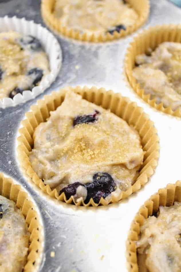 The vegan blueberry muffins prior to baking. The batter has been poured into a muffin pan which has been lined with paper baking cups. Each muffin has been garnished with demerara sugar.