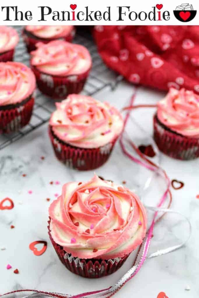 In focus is a single vegan chocolate cupcake with a two-toned (coral/ivory) vegan vanilla buttercream frosting piped into the shape of a rose. The cupcake is topped with red, white, and pink heart shaped sprinkles. In the background are 6 more cupcakes decorated the same way, 4 of which sit on a metal cooling rack in the upper left. In the upper right is a Valentine's Day themed tea towel. Scattered about are red heart confetti, the red, white, and pink heart shaped sprinkles, and intertwined red, white, and pink shimmery ribbons. Everything sits on a white marble background. At the top of the image are the words 'The Panicked Foodie,' with the i's colored red and dotted with red hearts. At the end is a black mixing bowl with a red heart on it that contains three sugar cubes.