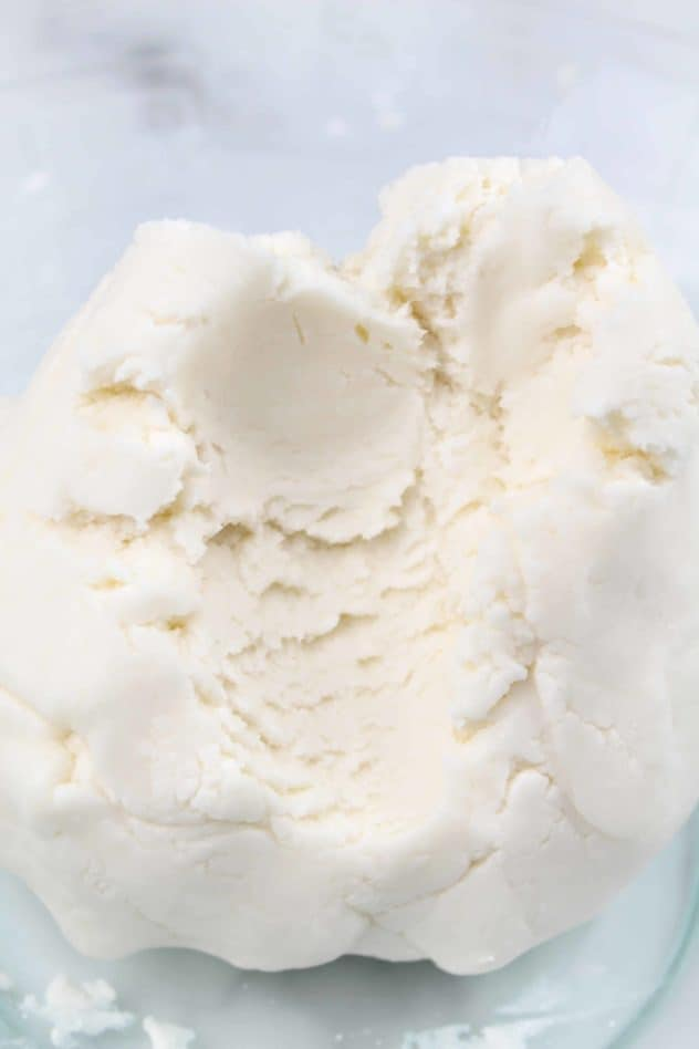 A dough consisting of confectioner's sugar, vegan butter, milk alternative, and vanilla extract sits in a large glass mixing bowl.
