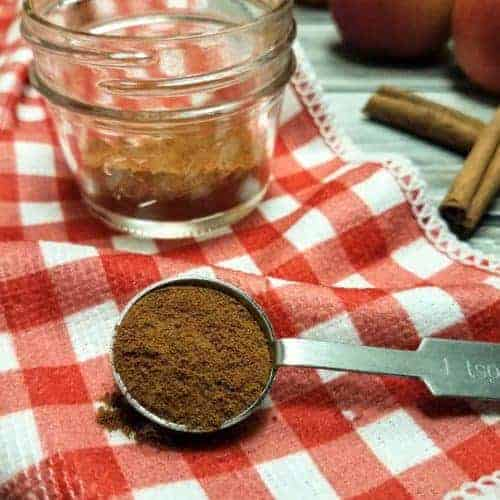 A teaspoon of apple pie spice sits in the foreground, with a jar of the spice, four apples, and two cinnamon sticks sit in the background. The jar and the teaspoon sit on a red and white checkered kitchen towel, whereas the apples and cinnamon sticks sit on a wood plank background. This is the vertical image.