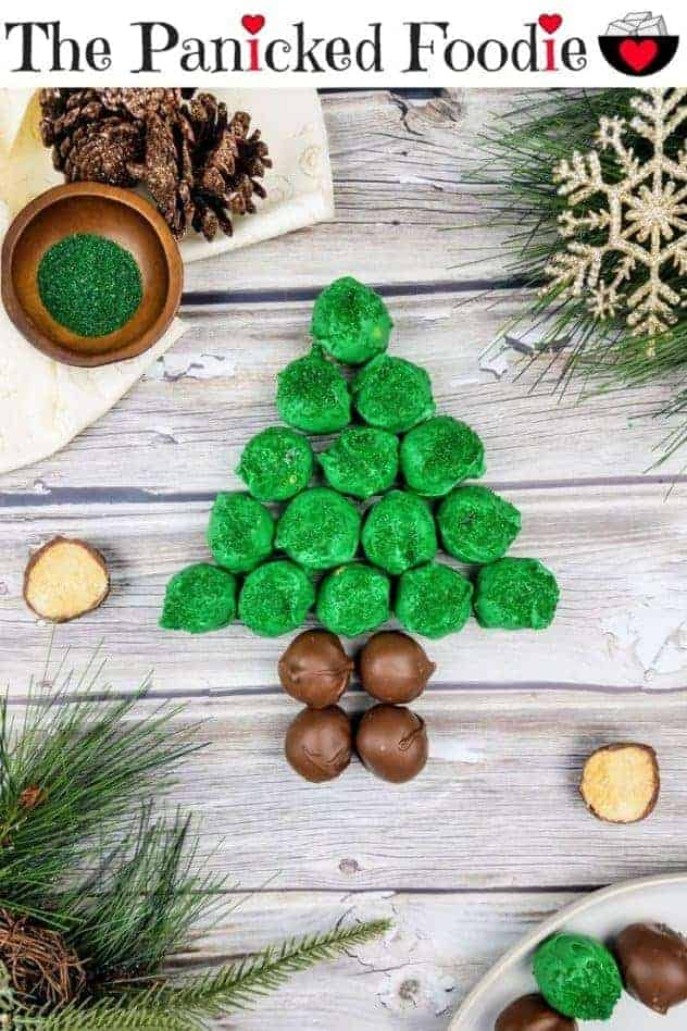 In the center are green and brown colored chocolate peanut butter balls arranged in the shape of a Christmas tree. Near the Christmas tree is an open peanut butter ball. Sprigs of fake evergreen trees sit in the lower left and the upper right. A gold snowflake also sits in the upper right. In the lower right are more peanut butter balls on a white plate. In the upper left is an ivory colored piece of cloth with gold glitter swirls, a cluster of pine cones, and a small dark brown wooden bowl of green sparkling sugar sprinkles. Everything sits on a wooden plank background. At the top of the image are the words 'The Panicked Foodie,' with the i's colored red and dotted with red hearts. At the end is a black mixing bowl with a red heart on it that contains three sugar cubes.
