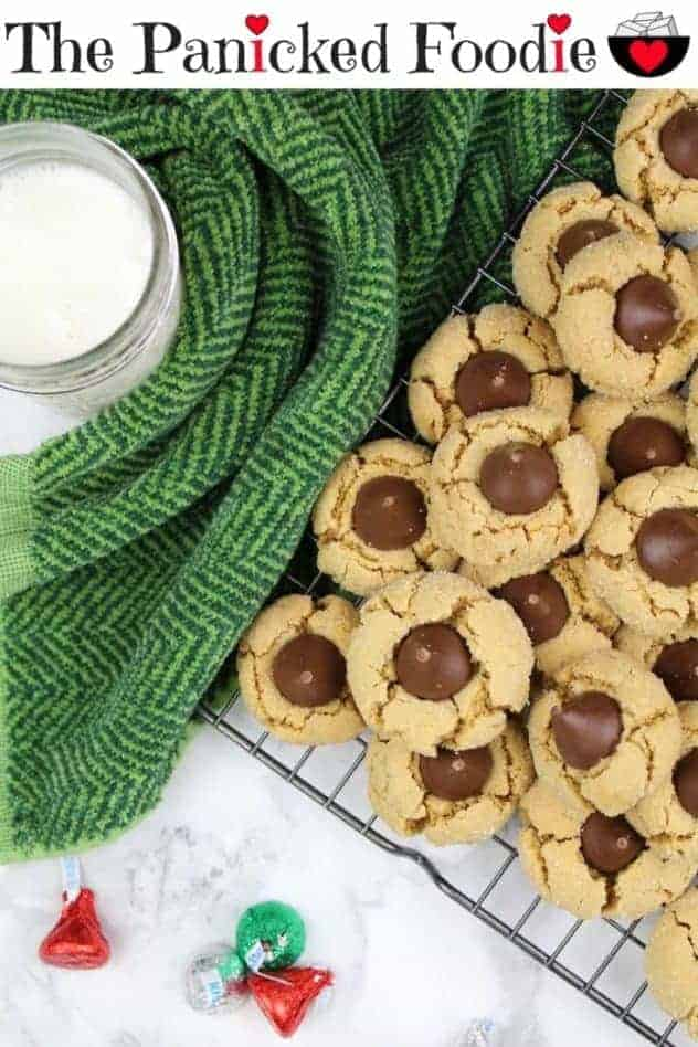 Healthier peanut butter blossoms sit on a wire cooling rack on the right side. On the left, is a glass of almond milk surrounded by a dark green kitchen towel. Scattered about at the bottom of the photo are red, green, and silver foil wrapped Hershey kisses. At the top of the image are the words 'The Panicked Foodie,' with the i's colored red and dotted with red hearts. At the end is a black mixing bowl with a red heart on it that contains three sugar cubes.