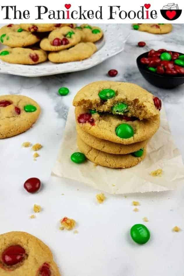 A stack of M&M cookies sits on a square of parchment paper. The top cookie is broken in half to show the inside texture. In the background is a white plate with a pile of cookies and a small black bowl containing red and green M&Ms. Scattered about in the photo for texture are cookie crumbs, additional cookies, and red and green M&Ms. Everything sits on a white marble background. At the top of the image are the words 'The Panicked Foodie,' with the i's colored red and dotted with red hearts. At the end is a black mixing bowl with a red heart on it that contains three sugar cubes.
