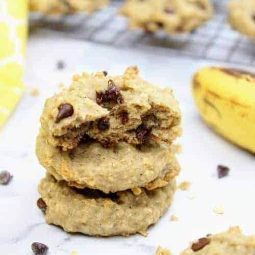 In the center of the photo is a stack of three vegan banana cookies with the top one cut in half to show the interior. To the left is a yellow tea towel and to the right is a very ripe banana. In the background are more vegan banana cookies cooling on a wire rack. Scattered about are mini chocolate chips, quick oats, and cookie crumbs. Everything sits on a white marble background.