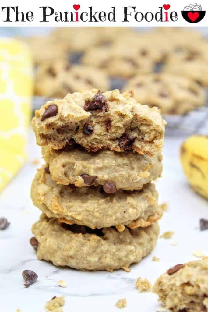 In the center of the photo is a stack of four vegan banana cookies with the top one cut in half to show the interior. To the left is a yellow tea towel and to the right is a very ripe banana. In the background are more vegan banana cookies cooling on a wire rack. Scattered about are mini chocolate chips, quick oats, and cookie crumbs. Everything sits on a white marble background. At the top of the image are the words 'The Panicked Foodie,' with the i's colored red and dotted with red hearts. At the end is a black mixing bowl with a red heart on it that contains three sugar cubes.