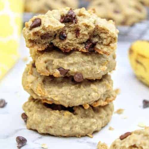 In the center of the photo is a stack of four vegan banana cookies with the top one cut in half to show the interior. To the left is a yellow tea towel and to the right is a very ripe banana. In the background are more vegan banana cookies cooling on a wire rack. Scattered about are mini chocolate chips, quick oats, and cookie crumbs. Everything sits on a white marble background.