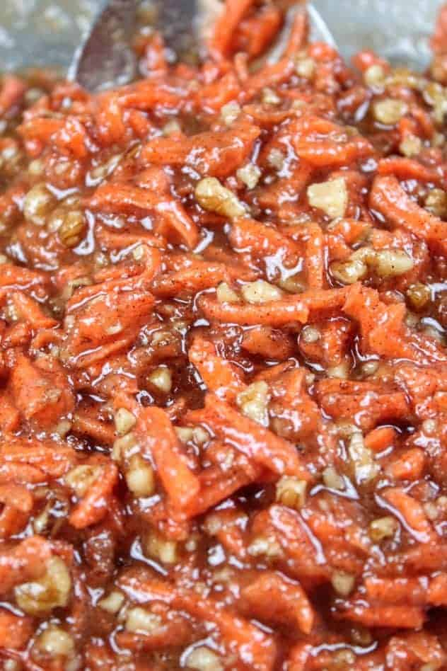 A mixture of unsweetened applesauce, granulated sugar, extra light olive oil, vanilla extract, shredded carrots, baking soda, baking powder, Kosher salt, ground cinnamon, ground all spice, and chopped walnuts in a large glass bowl.