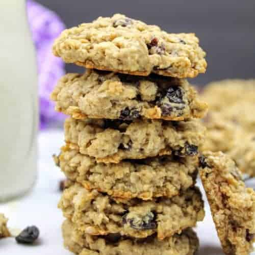 A stack of six vegan oatmeal raisin cookies sits in the center of the photo. Leaning against the stack on the right hand side is a half of a cookie to show the chewy interior. To the left of the stack, is a small glass of almond milk. In the background on the left is a purple tea towel and on the right are more cookies sitting on a cooling rack. Everything sits on a white marble background with a black vertical background. Scattered about are oat grains and raisins.