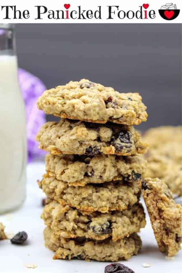 A stack of six vegan oatmeal raisin cookies sits in the center of the photo. Leaning against the stack on the right hand side is a half of a cookie to show the chewy interior. To the left of the stack, is a small glass of almond milk. In the background on the left is a purple tea towel and on the right are more cookies sitting on a cooling rack. Everything sits on a white marble background with a black vertical background. Scattered about are oat grains and raisins. At the top of the image are the words 'The Panicked Foodie,' with the i's colored red and dotted with red hearts. At the end is a black mixing bowl with a red heart on it that contains three sugar cubes.