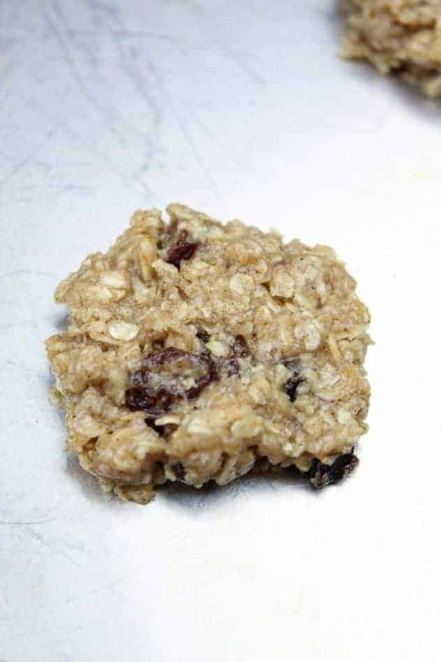 A single vegan oatmeal raisin cookie sits on a greased aluminum baking sheet prior to baking.