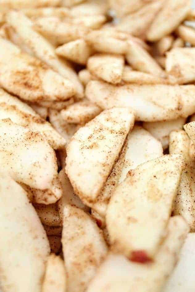 A close-up of apple slices coated with gluten-free flour and apple pie spice.