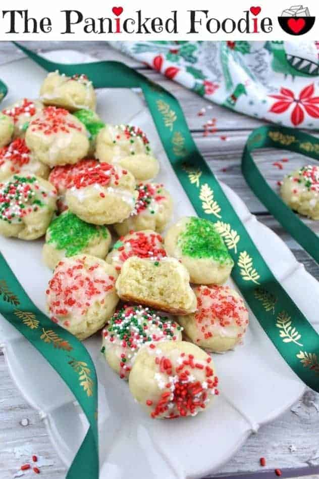 Gluten-free ricotta cookies sit on a scalloped cream colored serving tray. On top of the pile is half of a cookie to show the fluffy interior texture. A green ribbon with gold leaves weaves throughout the photo. In the upper right is a Christmas themed tea towel and one more gluten-free ricotta cookie. Scattered throughout the photo are red and white sprinkles. Everything sits on a wood plank background. At the top of the image are the words 'The Panicked Foodie,' with the i's colored red and dotted with red hearts. At the end is a black mixing bowl with a red heart on it that contains three sugar cubes.
