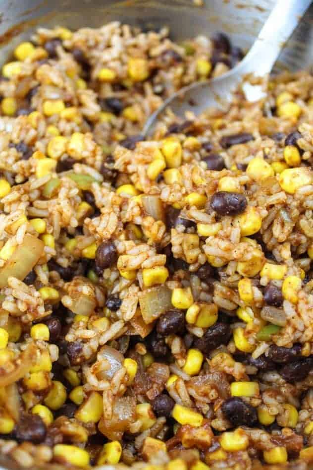 Brown rice with black beans and corn in a pan. A stainless steel spoon sits in the pan in the upper right hand corner.