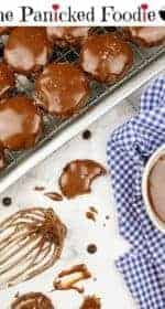 In the upper left are glazed vegan texas sheet cake cookies sitting on a cooling rack on a rimmed baking sheet. Next to the baking sheet is a wire whisk with chocolate glaze on it. On the right is a small white bowl containing the remainder of the chocolate glaze. The white bowl sits on a white and navy blue checkered tea towel. Scattered about are splatters of glaze, chocolate chips, and a half-eaten cookie. At the top of the image are the words 'The Panicked Foodie,' with the i's colored red and dotted with red hearts. At the end is a black mixing bowl with a red heart on it that contains three sugar cubes.