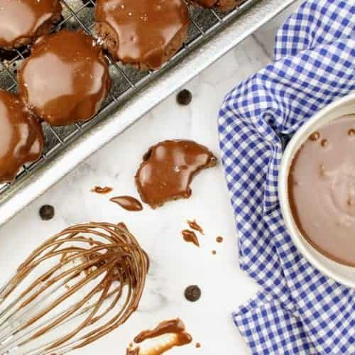 In the upper left are glazed vegan texas sheet cake cookies sitting on a cooling rack on a rimmed baking sheet. Next to the baking sheet is a wire whisk with chocolate glaze on it. On the right is a small white bowl containing the remainder of the chocolate glaze. The white bowl sits on a white and navy blue checkered tea towel. Scattered about are splatters of glaze, chocolate chips, and a half-eaten cookie.