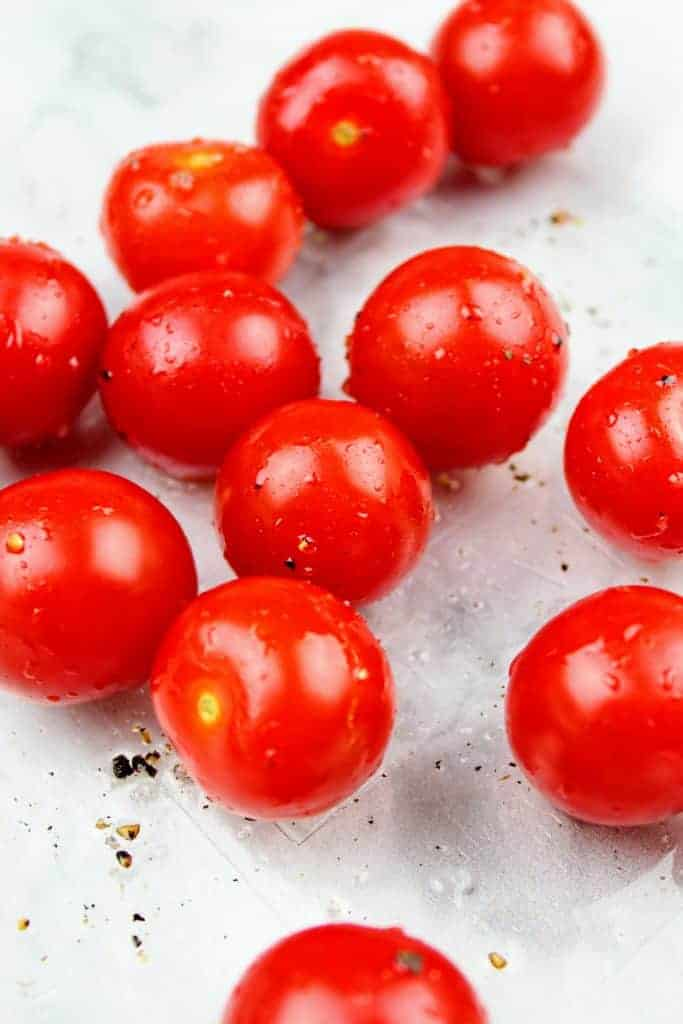 Cherry tomatoes drizzled with extra light olive oil and sprinkled with salt and pepper sit in a glass baking dish.