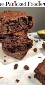 A stack of four dark chocolate avocado brownies sit on crinkled parchment paper with chocolate chips and chunks of brownie scattered about. There is also an avocado in the background. Everything sits on a white marble background, with a plain black background. At the top of the image are the words 'The Panicked Foodie,' with the i's colored red and dotted with red hearts. At the end is a black mixing bowl with a red heart on it that contains three sugar cubes.