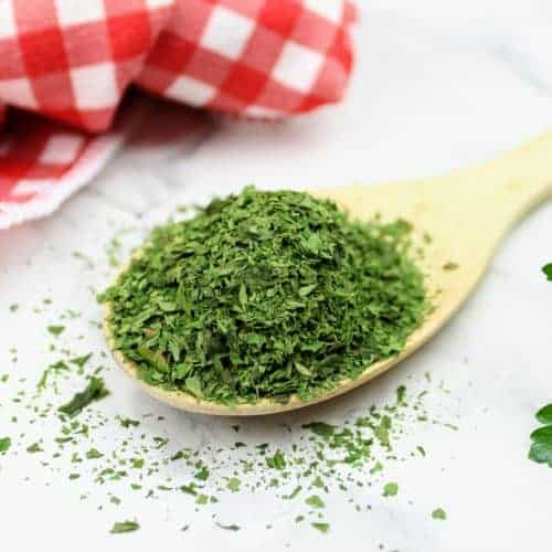 A finely crushed overflowing pile of dried parsley sits on a wooden spoon. In the lower right-hand corner are some fresh parsley leaves and in the upper left-hand corner is a red and white checkered tea towel.