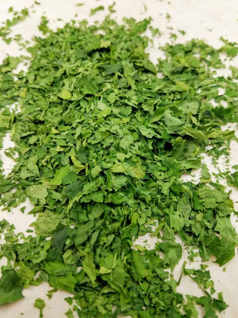 A finely crushed pile of dried parsley on a parchment-lined baking sheet.