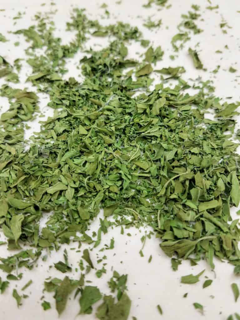 A finely crushed pile of dried Italian oregano on a parchment-lined baking sheet.