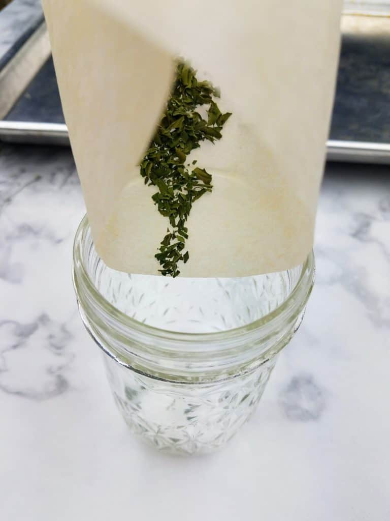 Pouring the finely crushed dried Italian oregano into a glass jar using the parchment paper as a funnel.
