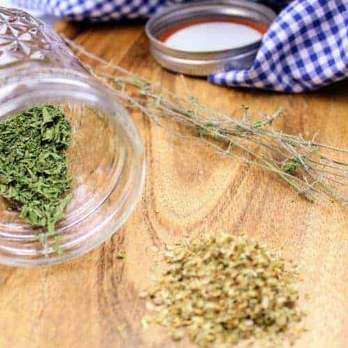 On the left side is the dried Italian oregano in a glass jar, and on the right is a pile of store-bought oregano to show how vibrant dried fresh oregano is. In the background are oregano stems, the lid to the glass jar, and a tea towel. Everything sits on a serving board.