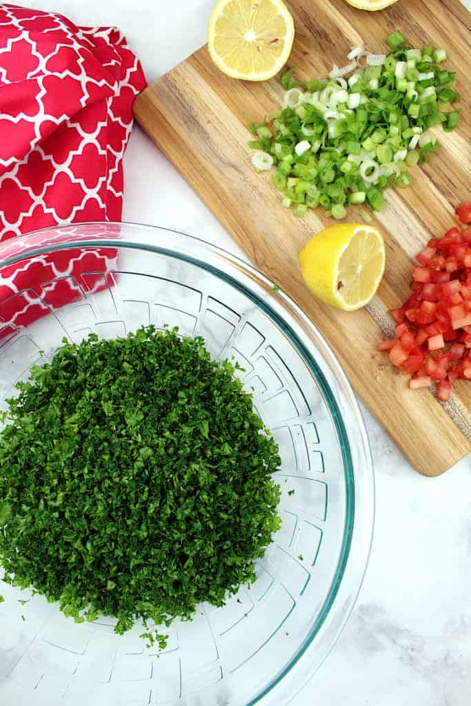 In the lower-left is a large bowl containing chopped parsley. In the upper right are halved lemons, a diced tomato, and chopped scallions all sitting on a cutting board. In the upper left is a tea towel.