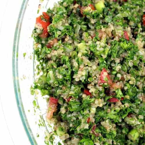 The finished quinoa tabbouleh in a large glass bowl.