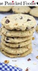 In the center sits a stack of vegan doubletree chocolate chip cookies. In the background are more cookies sitting on a cooling rack. On the left is a blue and white checkered tea towel. Scattered about the stack of cookies are walnuts, rolled oats, and chocolate chips. At the top of the image are the words 'The Panicked Foodie,' with the i's colored red and dotted with red hearts. At the end is a black mixing bowl with a red heart on it that contains three sugar cubes.
