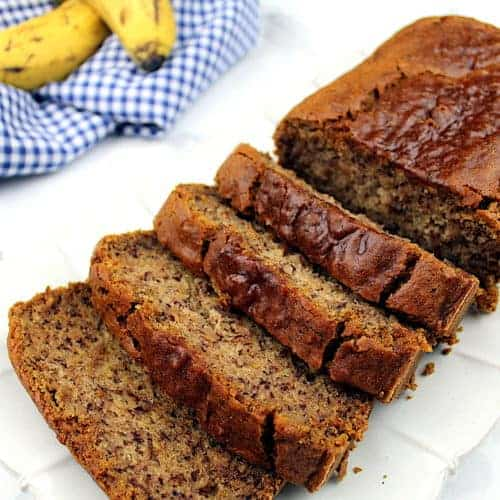 Vegan gluten-free banana bread sits on a platter. In the upper left is a tea towel with some bananas.