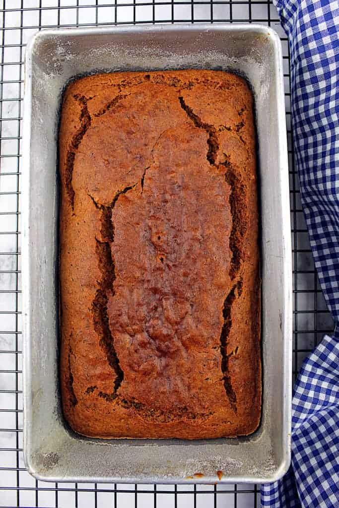 Baked vegan gluten-free banana bread sits in the bread pan on a cooling rack. A tea towel sits to the right.