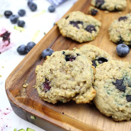 Gluten-free blueberry zucchini cookies sit on a bread board. Blueberries, shredded zucchini, and cookie crumbs are scattered about. A tea towel sits in the background.